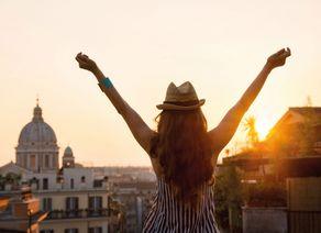 Frau hinter mit ausgestreckten Armen bei Sonnenuntergang in Rom iStock488600308 web